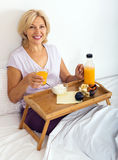 Счастливая зрелая женщина наслаждаясь завтраком Стоковое Изображение RF