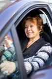 Счастливая зрелая женщина сидя в новом автомобиле Стоковая Фотография RF