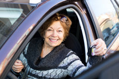 Счастливая зрелая женщина сидя в новом автомобиле Стоковые Изображения RF