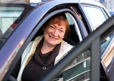 Счастливая зрелая женщина сидя в новом автомобиле Стоковое Изображение