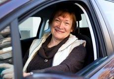 Счастливая зрелая женщина сидя в новом автомобиле Стоковое Фото