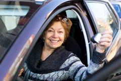 Счастливая зрелая женщина сидя в новом автомобиле Стоковые Фотографии RF