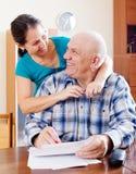 Счастливая зрелая пара заполняет внутри бумагу Стоковые Фото