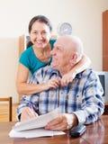 Счастливая зрелая пара заполняет внутри бумажный вопросник Стоковое Изображение RF