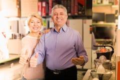 Счастливая зрелая пожененная пара в торговом центре покупает малое kitche Стоковые Изображения RF