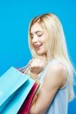 Счастливая изумляя блондинка с волосами Lond и очаровательной улыбкой на голубой предпосылке в студии Счастливая женщина держа мн Стоковая Фотография RF