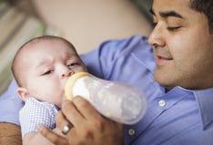 Счастливая испанская бутылка Feading отца его сын стоковая фотография rf