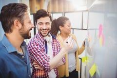 Счастливая исполнительная власть при коллеги готовя whiteboard на творческом офисе стоковые фотографии rf