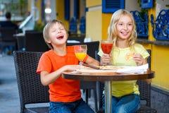 Счастливая или удовлетворенная девушка ширины мальчика есть пиццу и стоковое фото