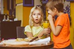 Счастливая или удовлетворенная девушка ширины мальчика есть пиццу и стоковые изображения rf