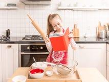 Счастливая кавказская девушка ребенка подготавливает испечь в кухне Стоковые Изображения