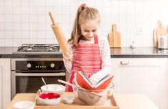 Счастливая кавказская девушка ребенка подготавливает испечь в кухне Стоковые Изображения RF