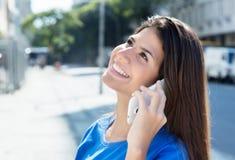 Счастливая кавказская женщина в голубой рубашке на телефоне Стоковые Фото