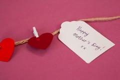 Счастливая карточка дня матерей и красные сердца вися на веревочке Стоковые Изображения RF