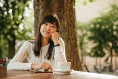 Счастливая китайская женщина на таблице кафа с цифровой таблеткой Стоковая Фотография
