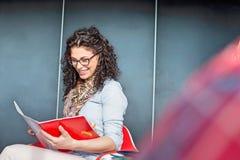 Счастливая книга чтения коммерсантки в офисе Стоковые Изображения RF