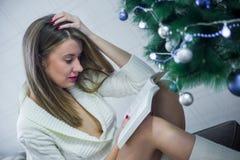 Счастливая книга чтения молодой женщины около рождественской елки, праздников Стоковые Фото