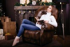 Счастливая книга чтения молодой женщины перед рождественской елкой стоковое фото