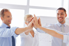 Счастливая команда дела давая максимум 5 в офисе Стоковая Фотография RF