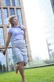Счастливая коммерсантка бежать на лужайке в городе Стоковое Фото
