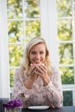 Счастливая коммерсантка держа кофейную чашку в кафе Стоковая Фотография RF