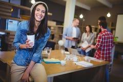 Счастливая коммерсантка держа устранимую чашку в офисе Стоковые Фото