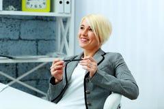 Счастливая коммерсантка ослабляя на ее рабочем месте Стоковые Изображения