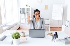 Счастливая коммерсантка показывая большие пальцы руки вверх на офисе Стоковое Изображение