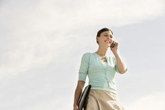 Счастливая коммерсантка связывая на мобильном телефоне против пасмурного Sk Стоковое фото RF
