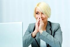 Счастливая коммерсантка сидя на ее рабочем месте и смотря прочь Стоковая Фотография RF