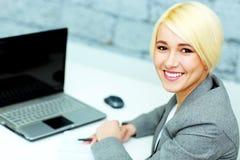 Счастливая коммерсантка сидя на ее рабочем месте с компьтер-книжкой Стоковые Фото