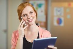 Счастливая коммерсантка смотря цифровую таблетку пока говорящ на телефоне Стоковое Изображение RF