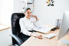 Счастливая коммерсантка yong сидя на ее рабочем месте держа eyeglasses Стоковые Изображения RF