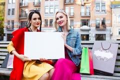 Счастливая концепция людей - красивые женщины с хозяйственными сумками Держите белый nameplate для вашего текста Стоковые Фотографии RF