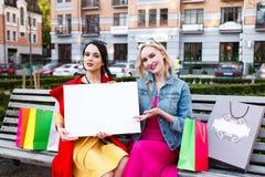 Счастливая концепция людей - красивые женщины с хозяйственными сумками Держите белый nameplate для вашего текста Стоковые Изображения