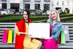Счастливая концепция людей - красивые женщины с хозяйственными сумками Держите белый nameplate для вашего текста Стоковые Изображения RF