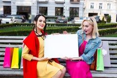 Счастливая концепция людей - красивые женщины с хозяйственными сумками Держите белый nameplate для вашего текста Стоковые Фото