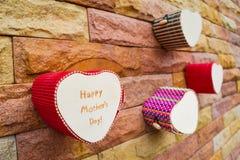 Счастливая коробка сердца дня матерей на кирпичной стене Стоковое Изображение RF