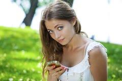 Счастливая красивая белокурая девушка вызывая телефоном в улице лета Стоковые Фото
