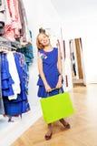 Счастливая красивая девушка в голубом платье на магазине Стоковое Фото