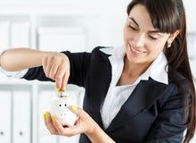 Счастливая красивая женщина кладя деньги штыря чеканит в белое piggyba Стоковые Изображения