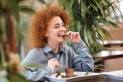 Счастливая красивая женщина сидя в кафе и есть десерт шоколада стоковые изображения
