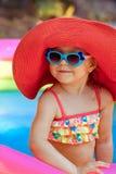 Счастливая красивая маленькая девочка в купальном костюме и шляпе плавает внутри Стоковое фото RF