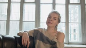 Счастливая красивая молодая женщина смеясь над пока смотрящ камеру Блондинка усмехается дома против окна сток-видео
