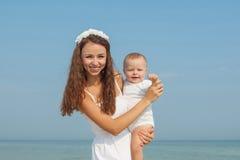 Счастливая красивые мать и сын наслаждаясь временем пляжа Стоковые Фото