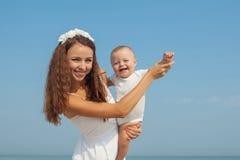 Счастливая красивые мать и сын наслаждаясь временем пляжа Стоковые Изображения RF