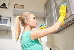 Счастливая кухня шкафа чистки женщины дома Стоковые Фото