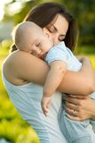Счастливая мать держа молодого спать сына Стоковое Изображение