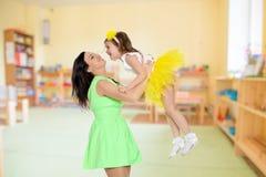 Счастливая мать держа молодую дочь Стоковая Фотография