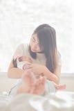 Счастливая мать держа прелестного младенца ребенка Стоковое фото RF